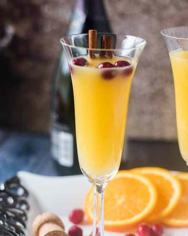 Mimosa in champagne glass with cinnamon sticks & cranberries