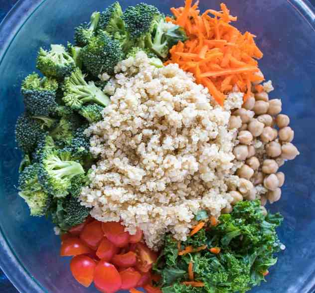 chopped kale, chickpeas, shredded carrots, chopped broccoli, chopped cherry tomatoes, and cooked quinoa in clear glass bowl.