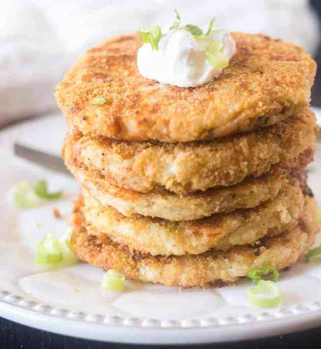 Mashed potato cakes stacked on a plate topped with sour cream and green onions.