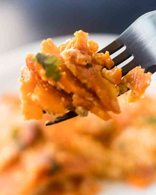 Spicy Scalloped Sweet Potatoes on a black fork