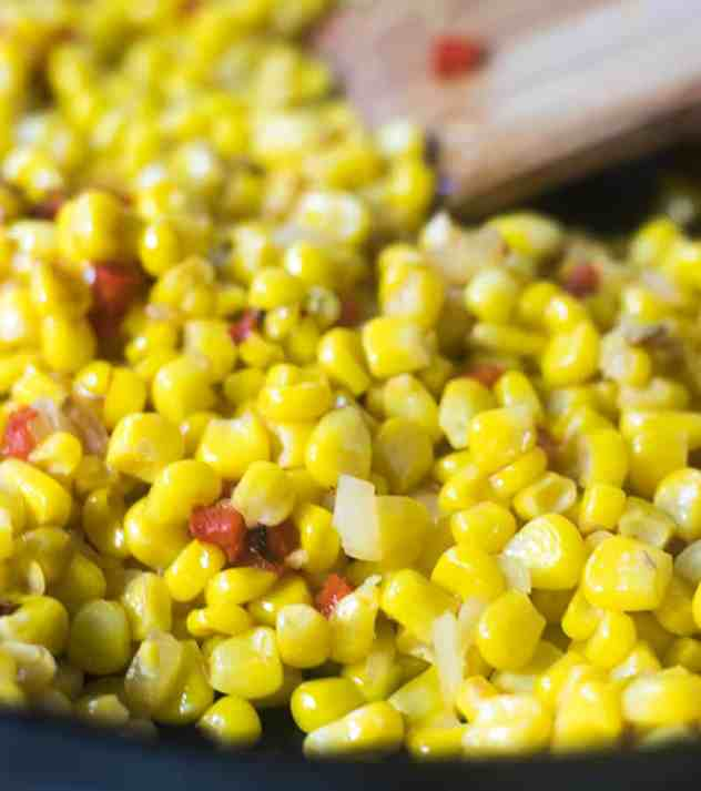 Corn, chopped onion, red bell pepper, & garlic in a skillet sauteed.