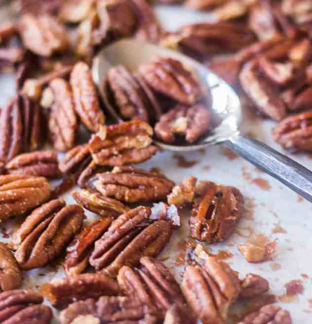 Maple Cinnamon Roasted Pecans on a sheet pan with parchment paper and a spoon,