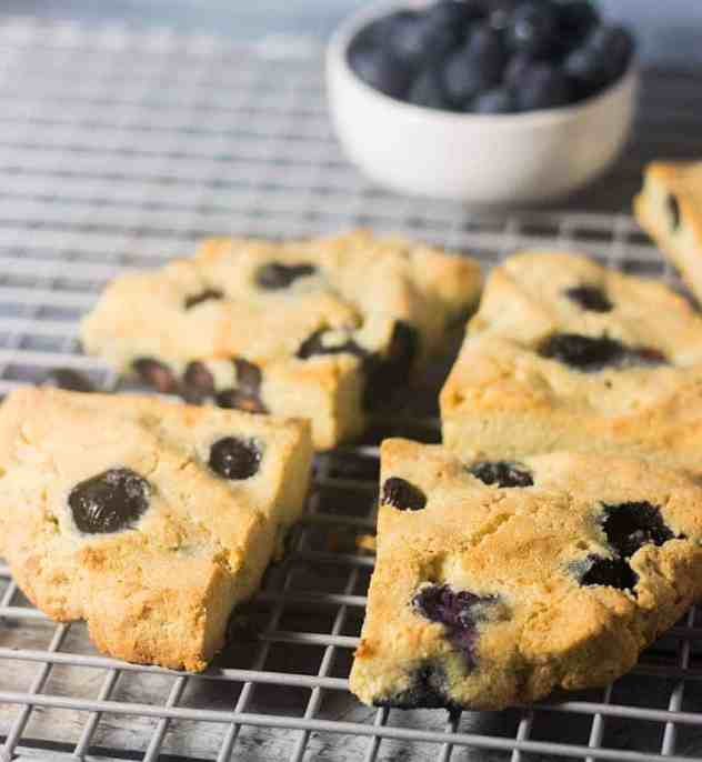 Blueberry Scones on a cooling rack with a bowl of blueberries