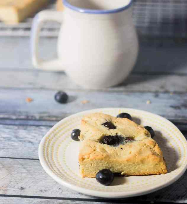 Blueberry Scone on a plate with some blueberries and coffee mug in background.
