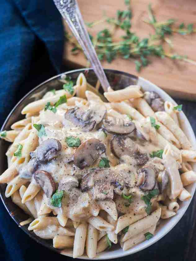 Mushroom Stroganoff in a bowl with a spoon garnished with parsley.