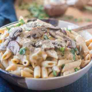 Mushroom Stroganoff sauce topped on penne noodles in a bowl.