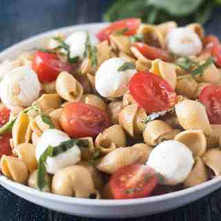 Caprese Pasta Salad in a white bowl with basil in background.