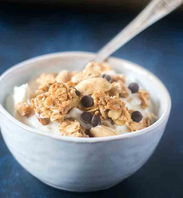 Peanut Butter Granola Clusters topped on greek yogurt in a white bowl with a silver spoon.