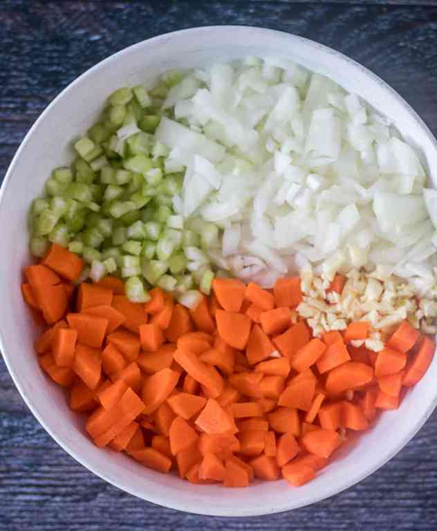 Chopped carrots, celery, sweet onion, and garlic in a white bowl.