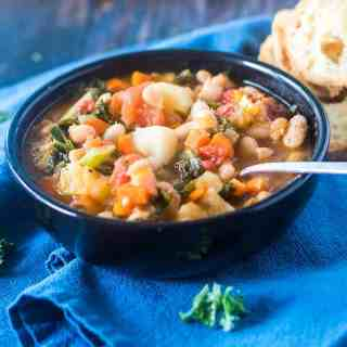 Bean stew loaded with an array of veggies including white beans, kale in a black bowl on a blue towel.
