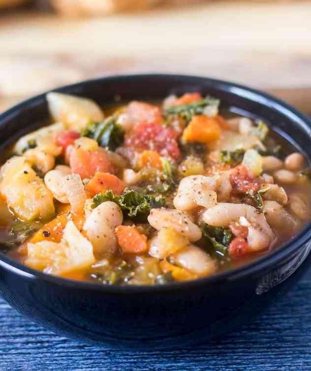 Bean Stew with Kale and white beans in a black bowl.