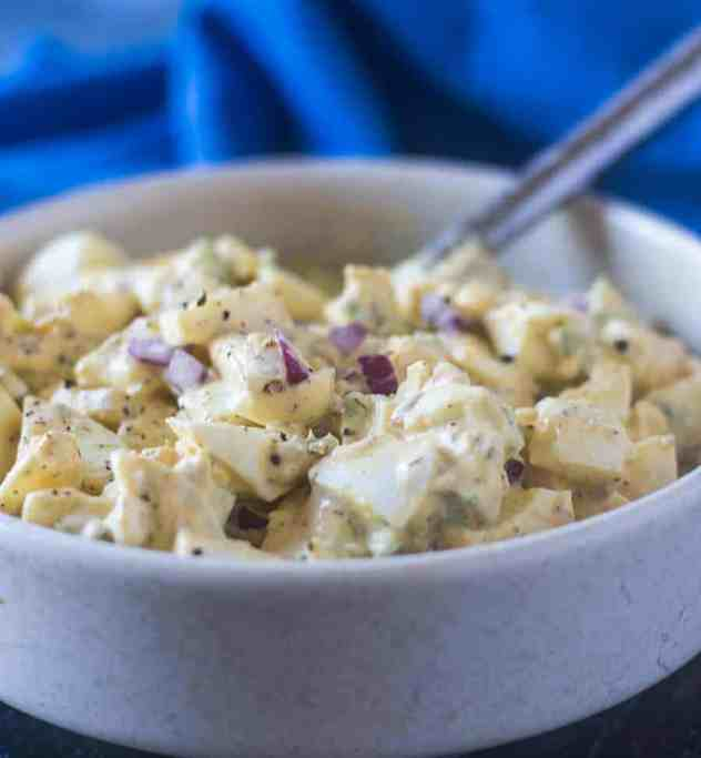 Egg Salad in a white bowl with a silver spoon and a blue napkin