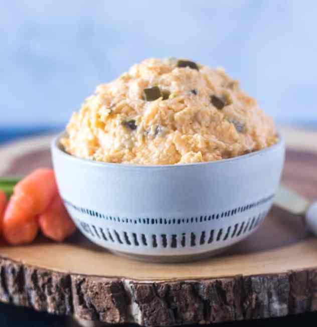 Jalapeno Cheese Dip in a white bowl with blue strips and carrots beside it on a wooden serving board.