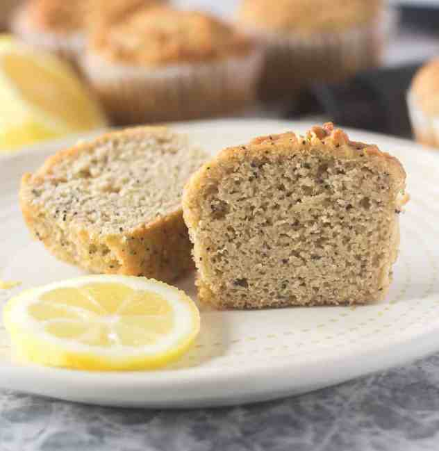 Lemon Poppy Seed Muffin cut in half on a plate with a lemon slice.