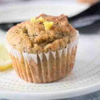 Lemon Poppy Seed Muffin on a white plate with yellow trim and topped with fresh lemon zest.