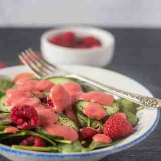 Spinach salad in a white bowl with cucumbers, raspberries and topped with raspberry vinaigrette and a bowl of raspberries in the background.