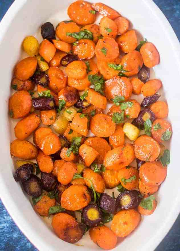 Multi colored maple glazed carrots in a casserole dish garnished with fresh parsley