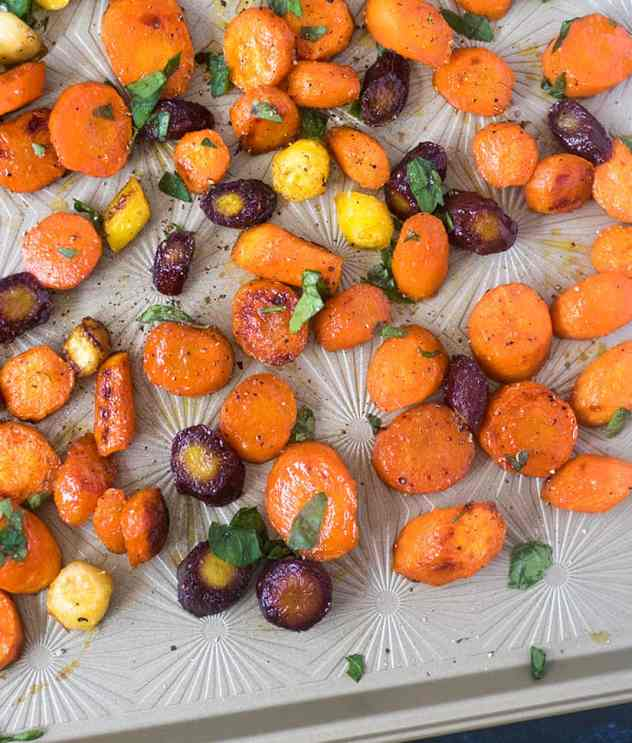 Multi colored maple glazed carrots on a baking pan garnished with fresh parsley
