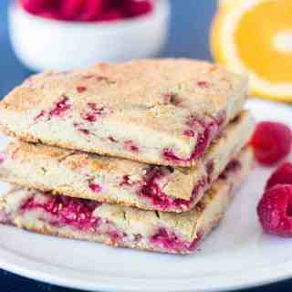 Raspberry Scones stacked on a white plate with fresh raspberries on plate and in the background.