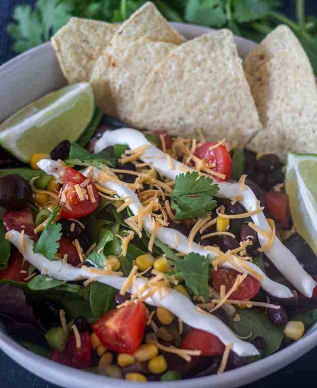 Black Bean Taco Salad in a bowl with toppings and tortilla chips