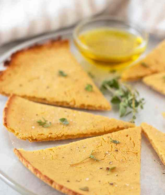 Socca on a serving plate with fresh herbs and a bowl of olive oil for dipping.
