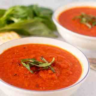 Vegan Tomato Soup in a white bowl garnished with fresh basil.