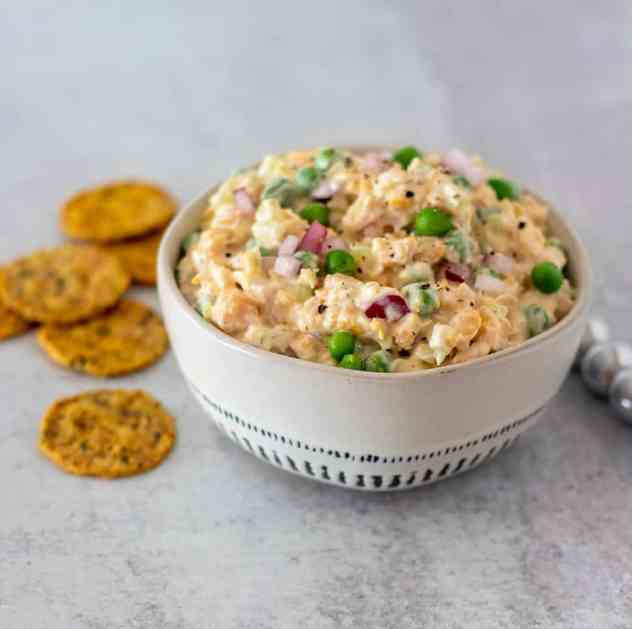 Chickpea salad in a white bowl with crackers for serving.