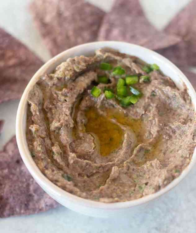 Black bean hummus in a white bowl with olive oil and chopped jalapeños