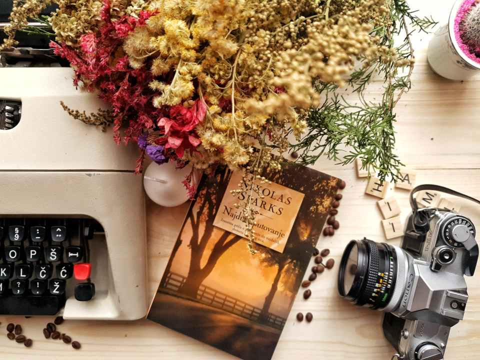 bunch of flowers and book arranged on wooden table with vintage typewriter and camera