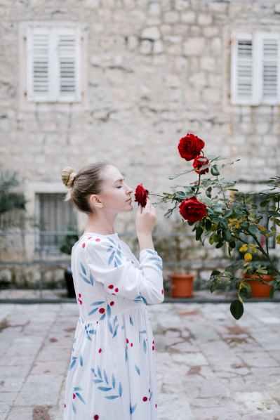 woman smelling flowers in street