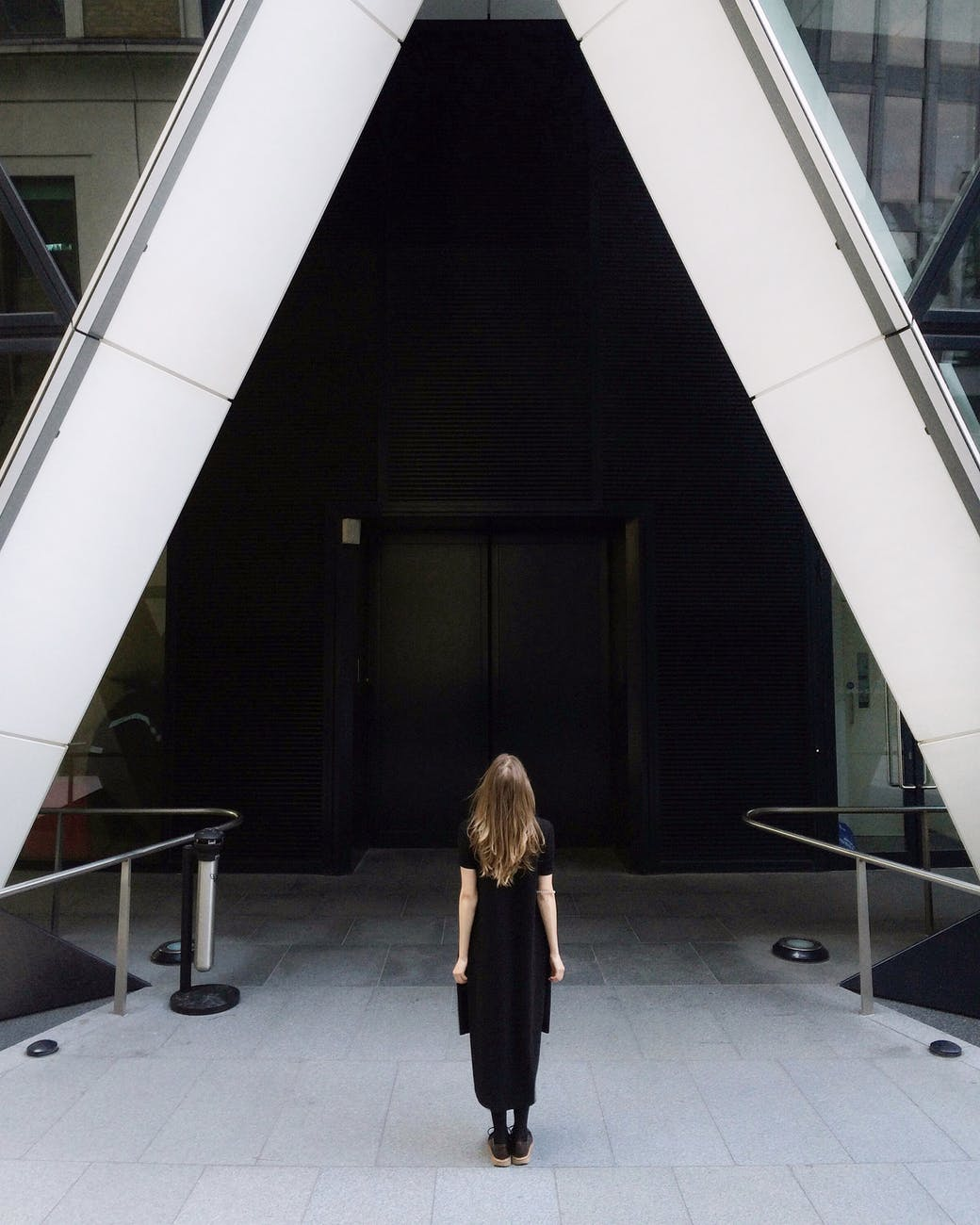back view of a woman in black dress standing in front of the building
