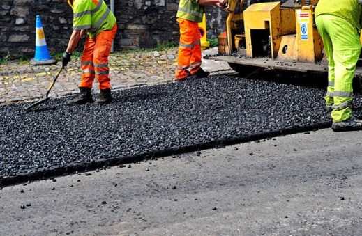workman-spreading-asphalt-during-road-resurfacing-dd3mn6