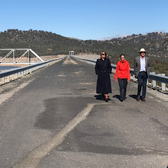 Minister for Water Melinda Pavey, Steph Cooke MP, and Mayor Bill West walk across the existing Wyangala Dam wall.