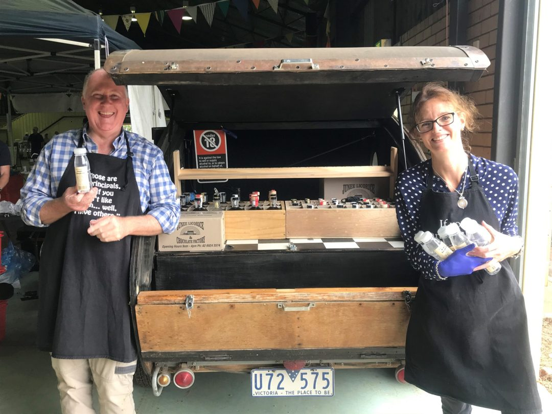 Neil Druce and Steph Cooke hold bottles of hand sanitiser in front of an open car boot. Both are smiling, wearing aprons and standing 1.5 metres apart.
