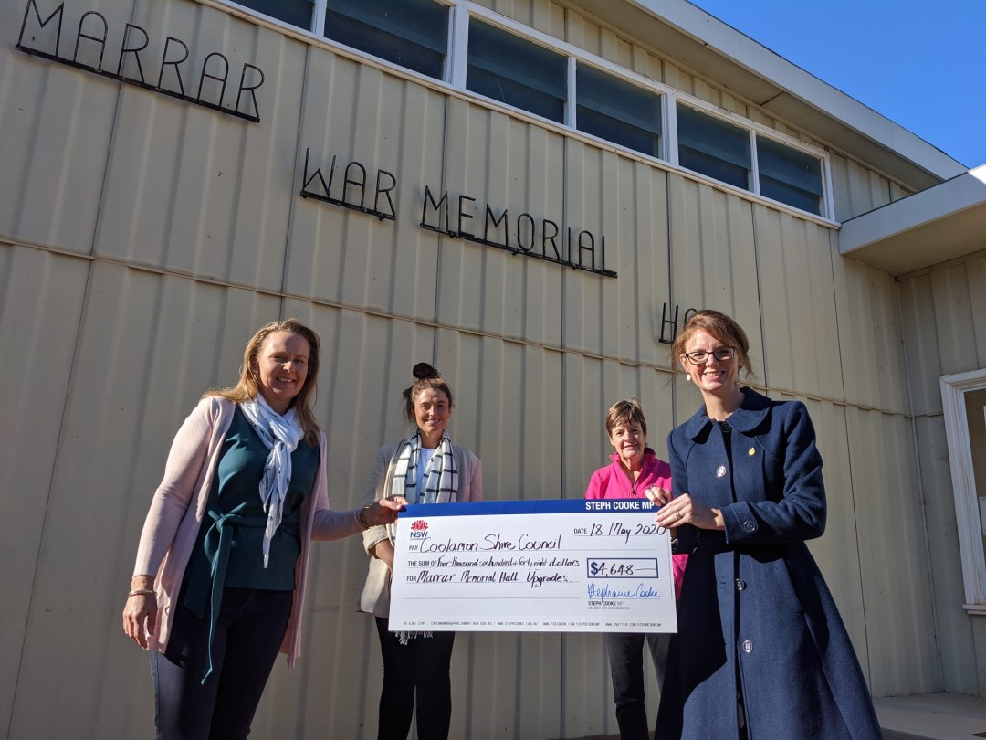 Joanne Langtry, Jess Inch, Vicky Langtry and Member for Cootamundra Steph Cooke hold a novelty sized cheque. They stand in front of a metal wall with a sign saying Marrar War Memorial Hall above them.