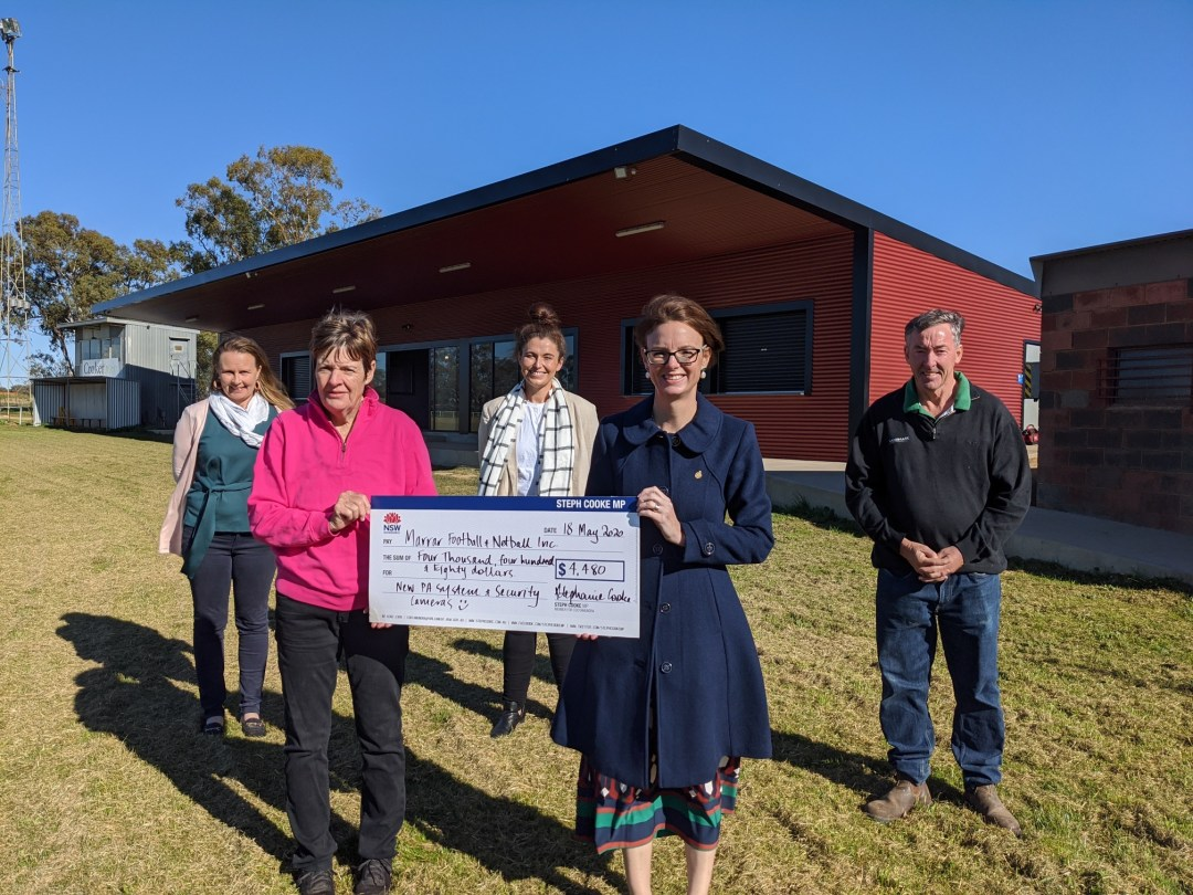 Joanne Langtry, Vicky Langtry, Jess Inch, Member for Cootamundra Steph Cooke MP and Terry Langtry hold a novelty cheque in front of the new club building.