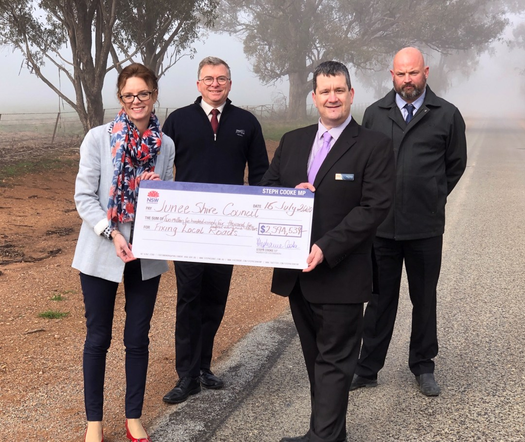 Steph Cooke, James Davis, Matt Austin stand on the side of a road and hold a large cheque. The weather is extremely foggy.