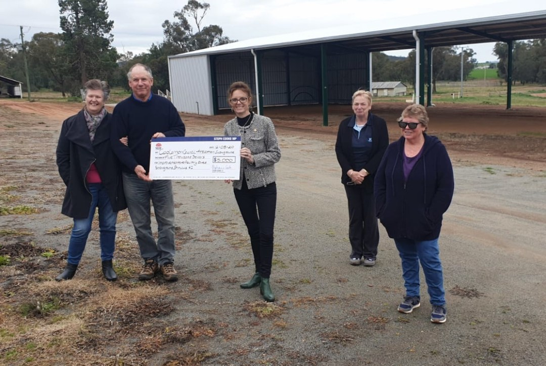 Steph Cooke and members of the Ardlethan Community hold a large cheque in front of a large, empty shed.
