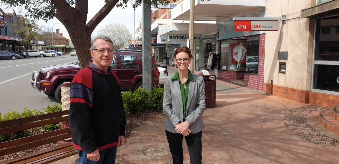 Daryl Quinlivan and Steph Cooke MP stand on the main street of Young, both smile at the camera.