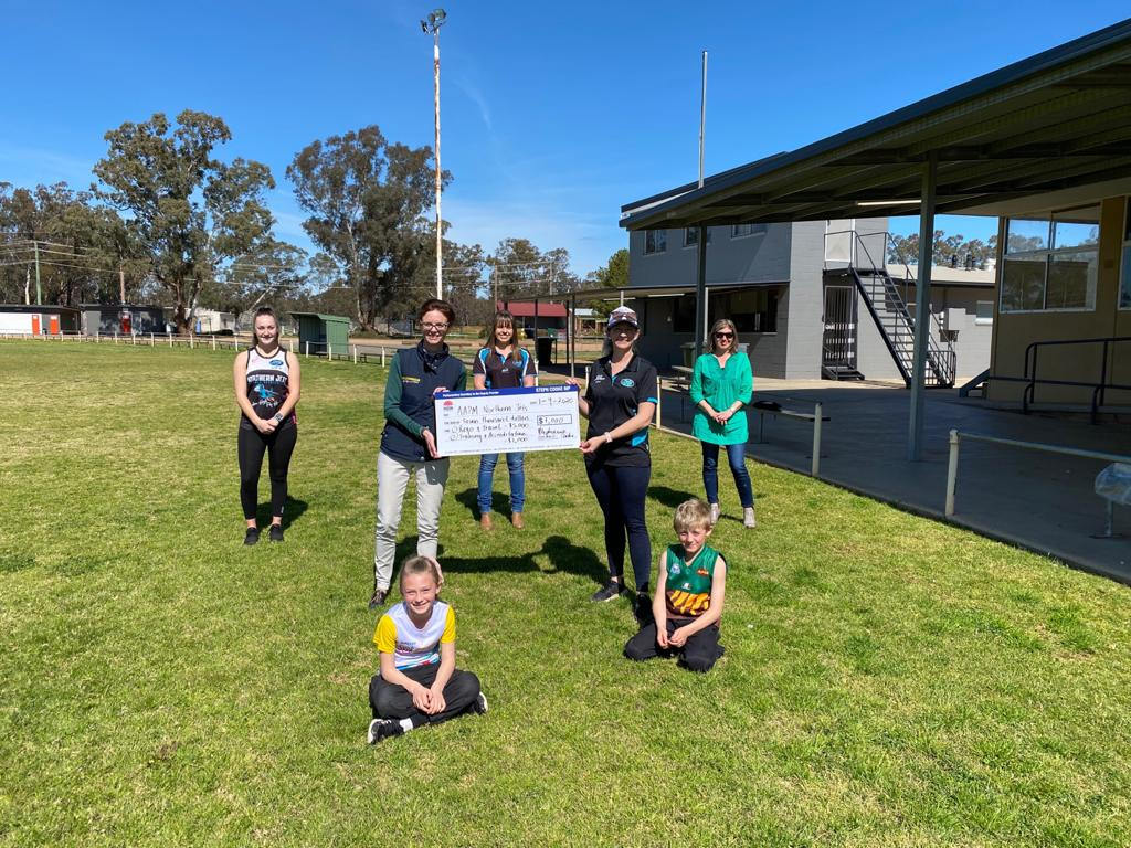 Steph Cooke presents a large cheque   to a group of people on a green football ground.