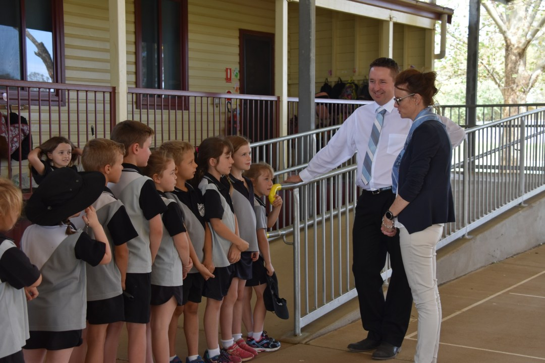 School children in uniform line up near a railing and speak to a teacher and Steph Cooke.