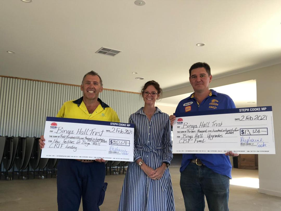 Nathan Kite, Steph Cooke MP and John Bianchini hold large cheques and stand in front of a corrugated iron wall inside the Binya Hall