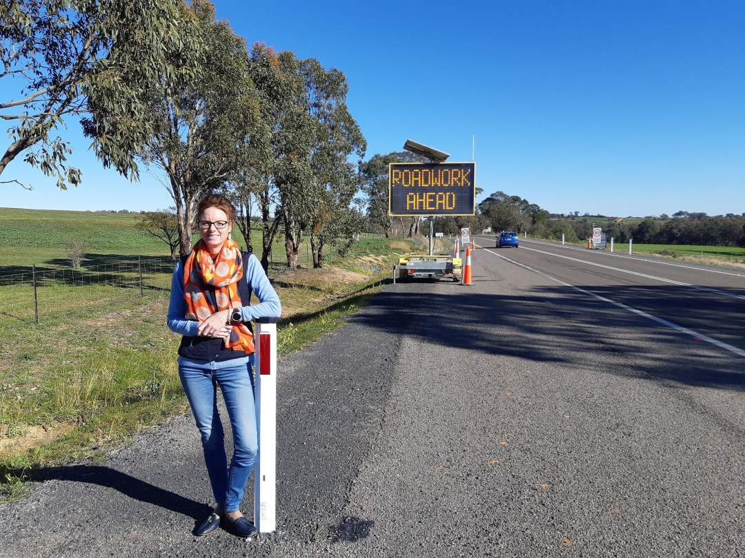 Steph Cooke leans on a guidepost on the side of the road and smiles at the camera. Behind her is a sign that reads roadwork ahead.