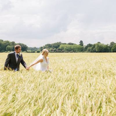 Norfolk wedding photographer – bride and groom walking through field