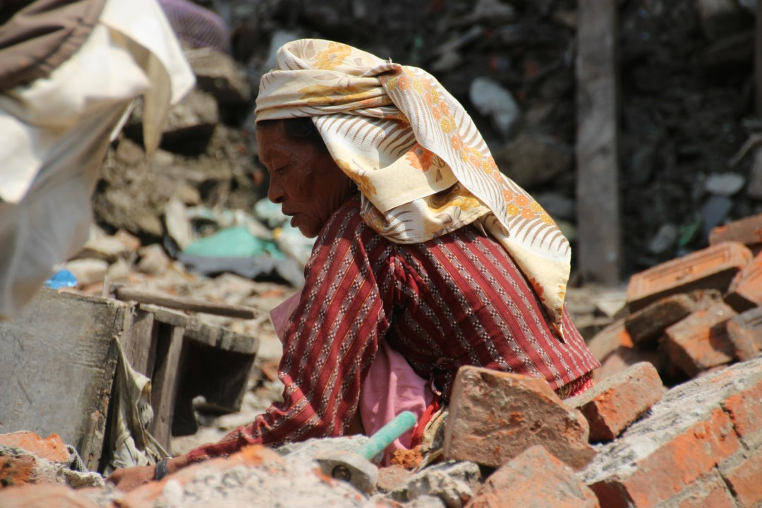 A local woman slowly clears the rubble of her home.