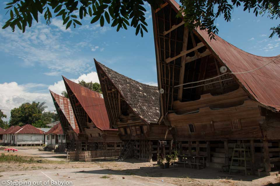 the Batak cultural identity is still visible in the characteristic architecture of the wooden houses with pointy and steep roofs, and proudly decorated with woodcarving motifs, painted in white, black and red