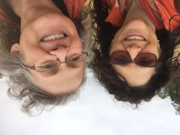 Two women friends taking a selfie. One is a bit older with grey hair, the other with brown hair.
