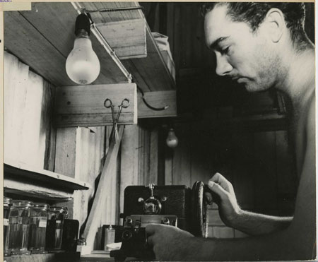 Pvt. Fred L. Walling. Operating a microtome, which is used for cutting thin sections of tissue and bone; these thin sections are placed on microscope slides and are used for the diagnosis of the cause of death. New Guinea. 02/16/1943.