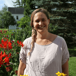 staff bio photo of Administrative Assistant Amalia Harris, standing and smiling in front of a colorful garden and a spruce tree in summertime