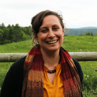 photo of Assistant to the President Heather Jerrett, standing and smiling in a green pasture with the green mountains in the background